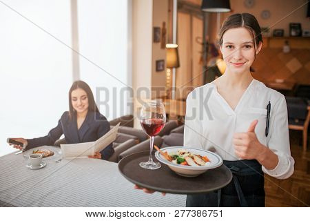 Cheerful Ypung Waitress Hold Tray With Food And Drink On It. She Look On Camera And Smile. Young Wom