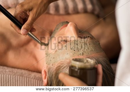 Closeup of beautician hands holding jar and applying mud mask on face of mature woman with brush. Beauty therapist applying purifying clay on senior woman face. Close up face of woman mud clay mask.