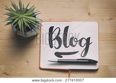 Blog. Blogging Concept With A Paper Notebook On The Wooden Desk, Top View.