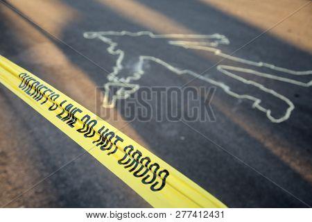 Crime Scene. Chalk Outline. Santa Claus Chalk Outline in the street.  Yellow Sheriff Do Not Cross Tape.