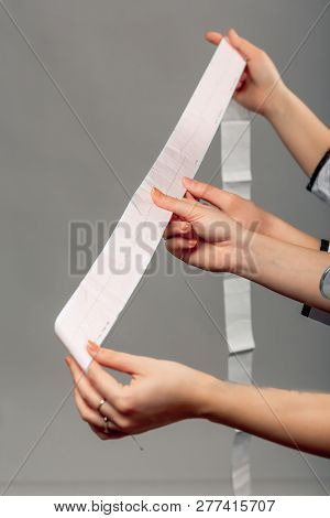 Hands Of Cardiologist Doctor And Medical Nurse Holding Ekg Paper Print With Cardiology Textbook On T