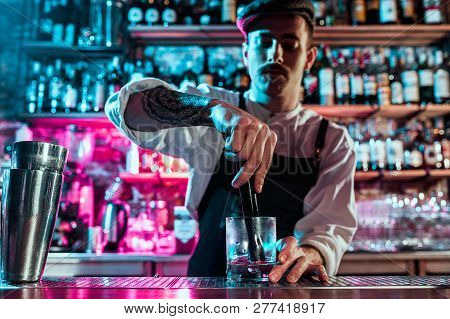 Expert Barman Is Making Cocktail At Night Club Or Bar. Glass Of Fiery Cocktail On The Bar Counter Ag