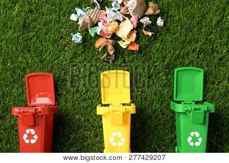 Trash Bins And Different Garbage On Green Grass, Top View. Waste Recycling Concept