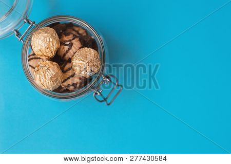Jar With Sweets Wrapped In Golden Foil And Cookies On Blue Background, Top View