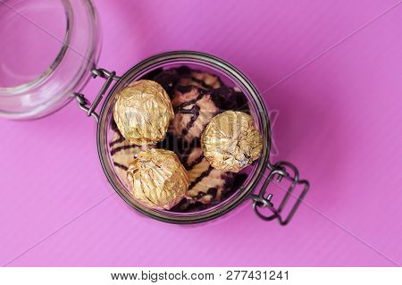 Glass Jar With Sweets And Cookies On Purple Background, Top View