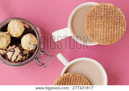 Two Coffee Cups With Dutch Caramel Waffles And Jar With Sweets And Cookies, Top View, Pink Backgroun