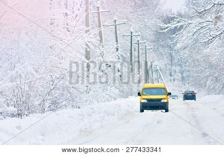 Snow Covered Road. Yellow Car On A Snowy Road. Winter Driving On Slippy Road.