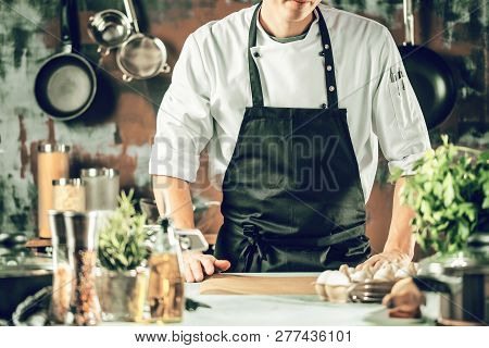 Cooking, Profession And People Concept - Male Chef Cook Making Food At Restaurant Kitchen.