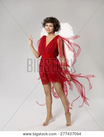 Woman Angel In Cupid Wings Costume, Happy Fashion Model In Red Dress, Beauty Girl Over White Backgro