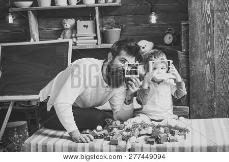 Nursery with chalkboard on background. Father and son play with constructor. Fatherhood concept. Family play with constructor at home. Dad and child play with details of constructor, looking through. poster