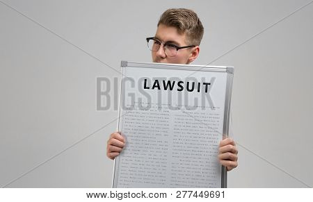 Young Man Keeps In Front Of Him A Poster With The Inscription Lawsuit Isolated On A Light Background