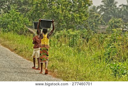 African Teenagers Carry A Luggage On Their Heads. Young African Girls Walk Along The Road. Countrysi