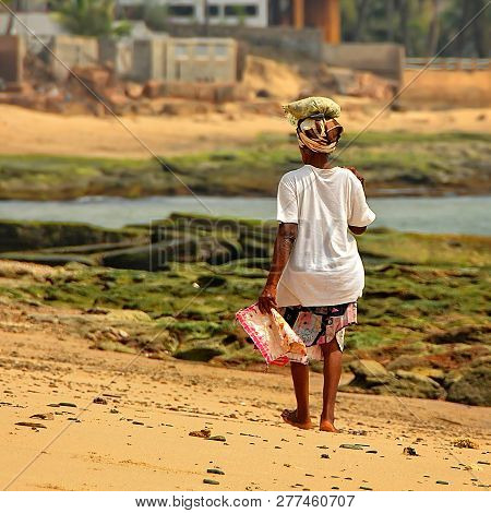 African Woman Carries A Luggage On Her Head. The Middle Aged Woman Walks Along The Ocean Shore. Life