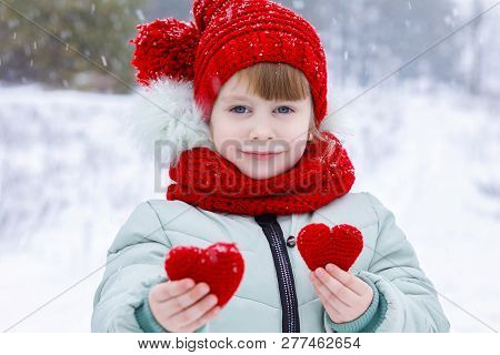 A Small Child Is Showing Two Little Hearts.