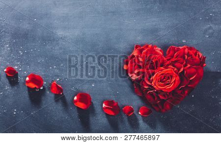 Heart-shaped red roses on stone background. Valentine's Day. Symbol of love and romance. Copyspace.