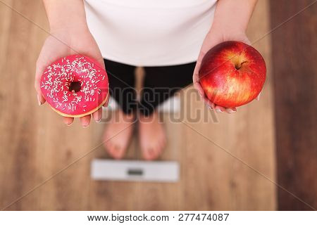 Diet. Woman Measuring Body Weight On Weighing Scale Holding Donut And Apple. Sweets Are Unhealthy Ju