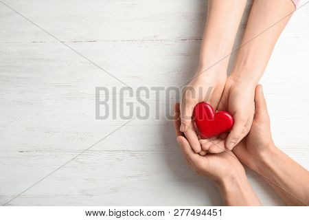 People Holding Red Heart On Wooden Background, Top View With Space For Text. Cardiology Concept