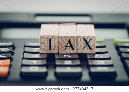 Tax Calculation Or Submission Concept, Small Wooden Stamp With Alphabet Combine The Word Tax On Blac