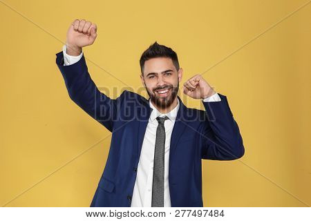 Happy Young Businessman Celebrating Victory On Color Background
