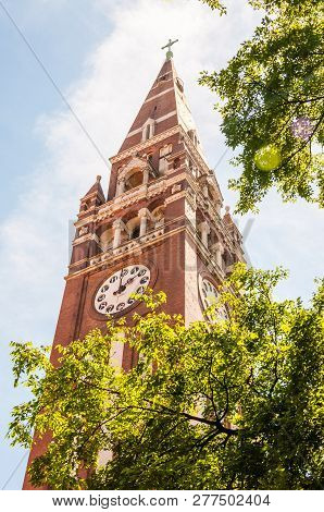 Szeged, Hungary - June 18, 2013: The Tower Of The Votive Church With Clock From Below. The Votive Ch