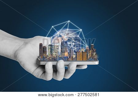 Smart Technology, Smart City And Network Technology. Hand Holding Mobile Smart Phone With Buildings