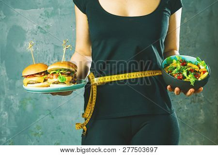 Healthy Young Woman Looking At Healthy And Unhealthy Plates Of Food, Trying To Make The Right Choice