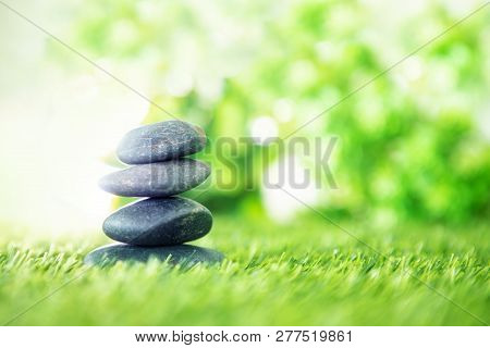Balance  With Pyramid Of Stone On Fresh Nature Green Grass  , Spa Meditation Or Well-being With Zen