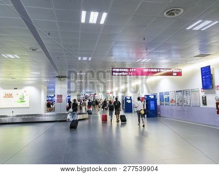 Bergamo, Italy - July 16 2018: Passengers Walk At The Baggage Claim Of Milan Bergamo Airport. Uniden
