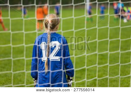 Girls Soccer Team Kicking Match On The Pitch. Girl Soccer Goalkeeper Plays Football. Young Girl As A