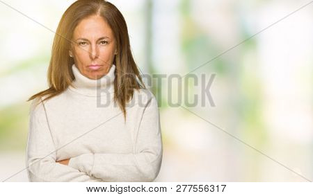 Beautiful middle age adult woman wearing winter sweater over isolated background skeptic and nervous, disapproving expression on face with crossed arms. Negative person.