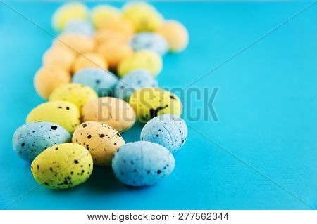 Easter Holiday Concept. Multicolored Miniature Eggs Close-up On A Blue Background. Miniature Eggs An