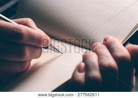 Close Up Of Woman's Hand Writing In Notebook