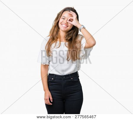 Young beautiful brunette business woman over isolated background doing ok gesture with hand smiling, eye looking through fingers with happy face.