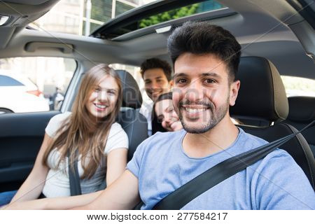 Group of happy friends sharing the same car for a trip