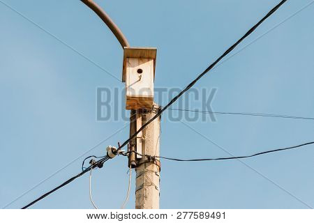 Lamppost With Wooden Birdhouse. Wires For Electricity In The Lantern. Blue Sky