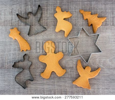 Top View Of Shaped Cookies Or Gingerbreads And Metal Cutters On Wooden Table