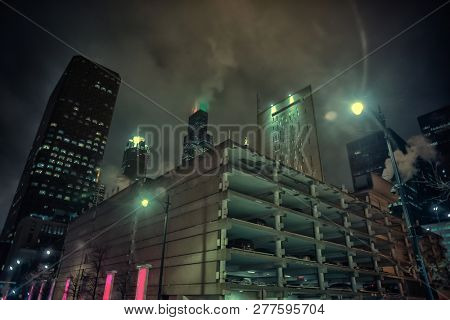 Dark and gritty Chicago city skyline at night during fog