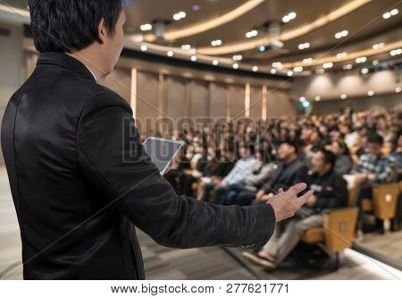 Rear View Of Business People Conference Speaker On Over The Abstract Blurred Photo Of Conference Hal