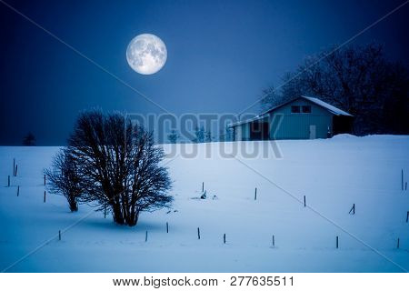 An image of a full moon winter scenery with a house