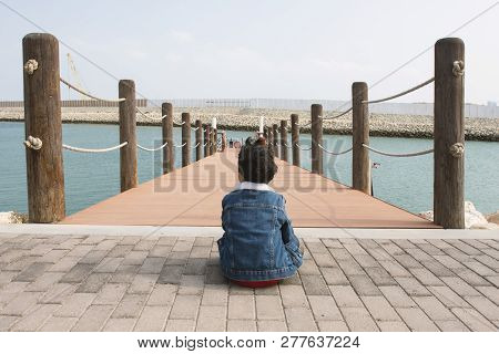 Little Boy Sitting Into The Port And Waiting Boat