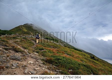 Hiker With Backpack Going Uphill. Hiker Going Up To The Mountain Peak On A Very Steep Trail.