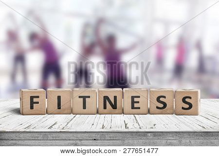Fitness Sign On A Table In A Gym With Women Training In The Background