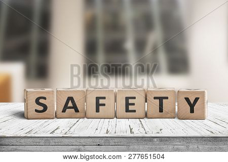 Safety Sign On A Wooden Desk In A Room With Covered Windows In The Background