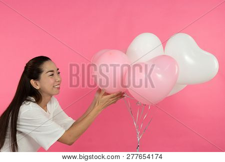 Woman In White Dress With Balloon Heart Shape Isolated On Pink Background