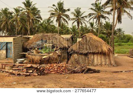 Barracks With Thatched Roof With Household Items In A Yard With Palm Trees In Background. Rural Life
