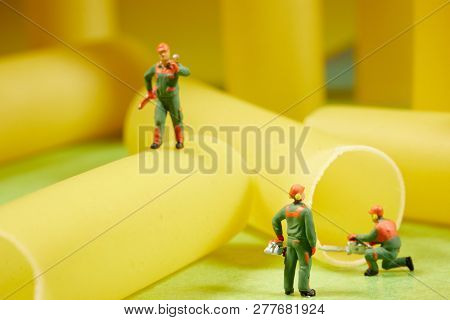 Miniature worker at work. Miniature worker work with spaghetti