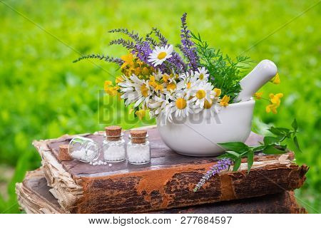 Mortar Of Healing Herbs, Bottles Of Homeopathic Globules And Old Book Outdoors. Homeopathy Medicine.