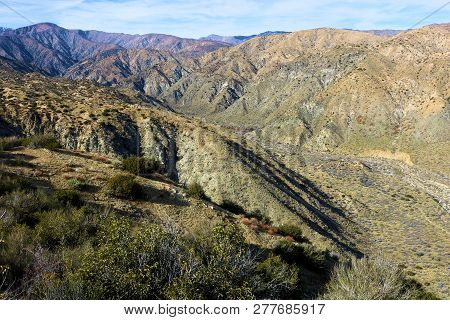 Arid landscape including arid mountains surrounding a canyon taken at badlands in the rural Colorado Desert, CA poster