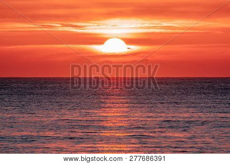 Sunrise Over The Ocean. Beautiful Seascape. Orange Sky Reflecting On Water At Dawn. Spiritual New Da