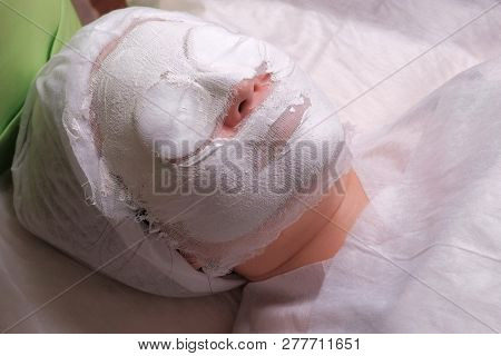 Woman in beauty salon with white mask on her face. The procedure of rejuvenation and cleansing of the skin in the cosmetology center. Spa therapy. Close-up. poster